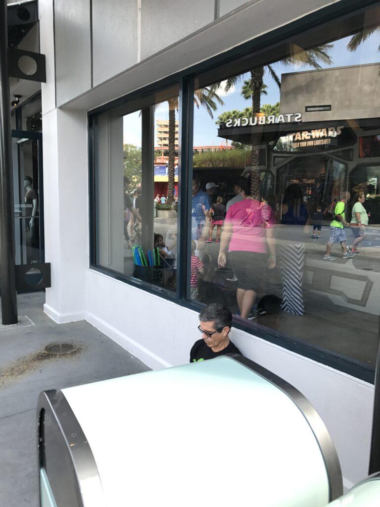 man sitting next to Disney shop