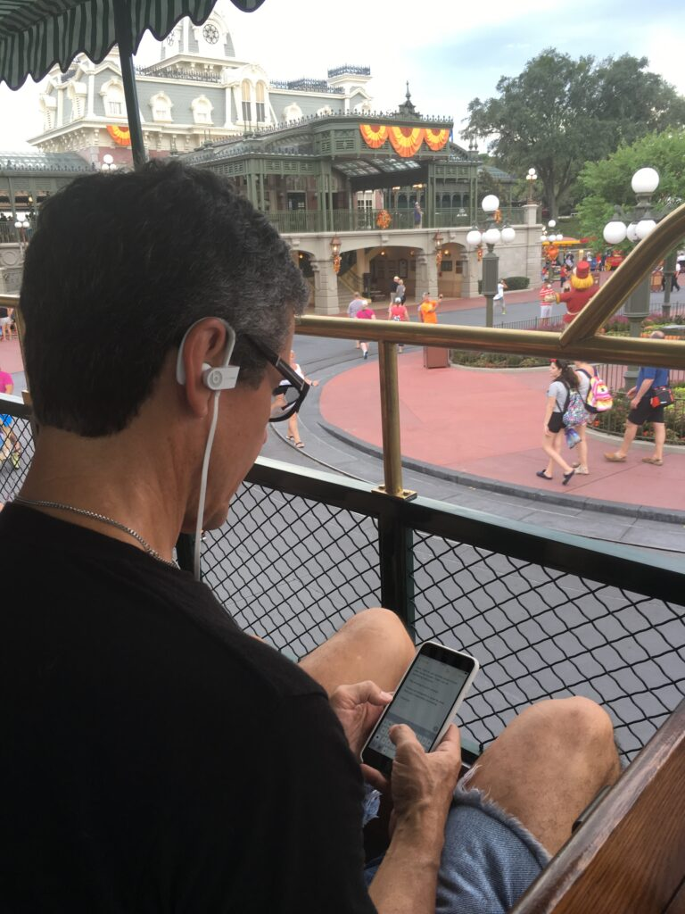 Man wearing head phones typing on phone at Disney