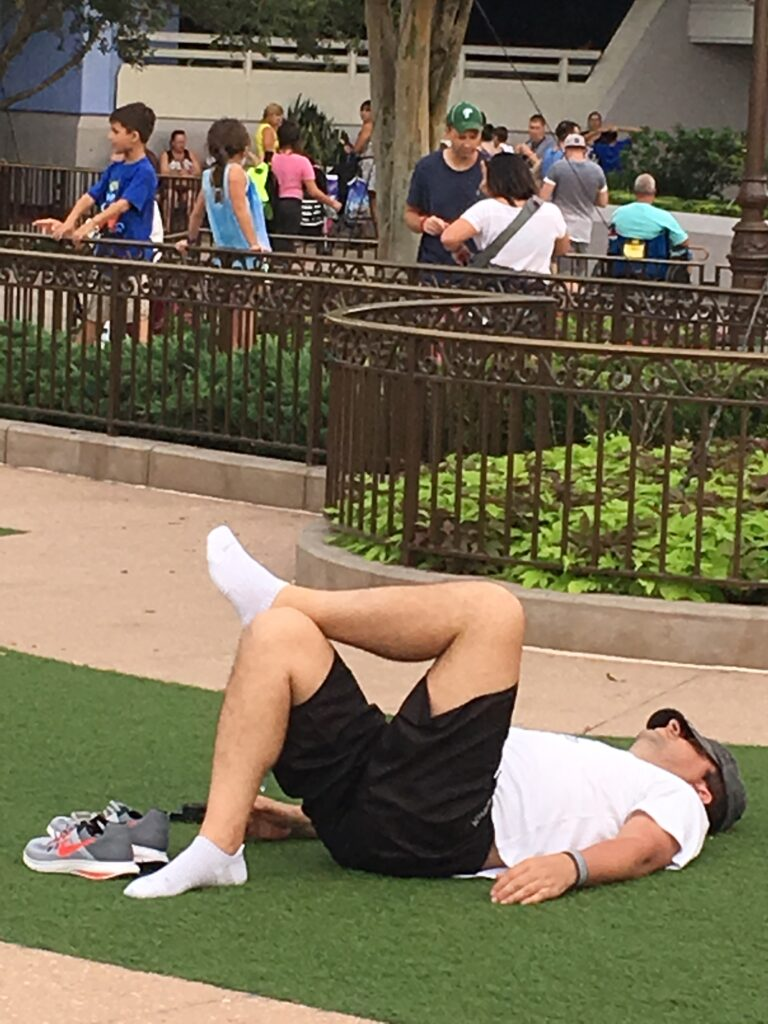 exhausted Guest resting on ground in Magic Kingdom