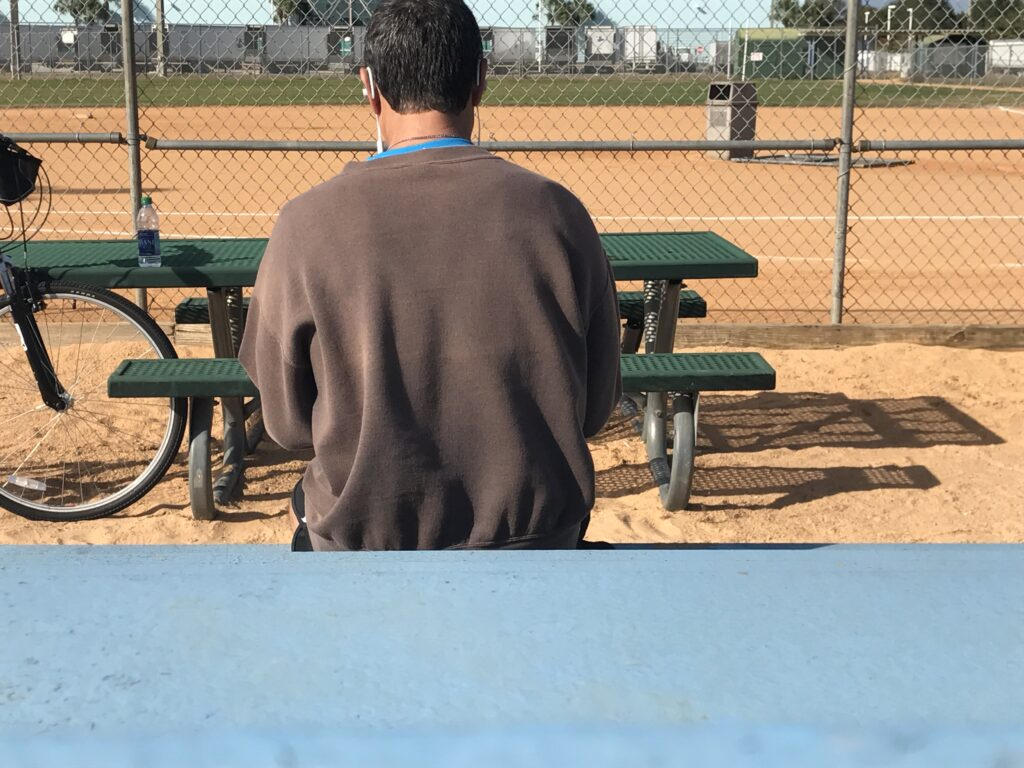 man with back turned at a softball field