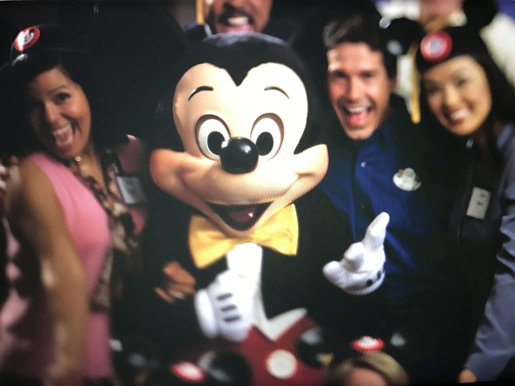 People surrounding Mickey Mouse for a photo
