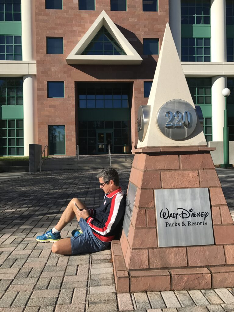 Disney author Jeff Noel sitting on ground writing on iPhone