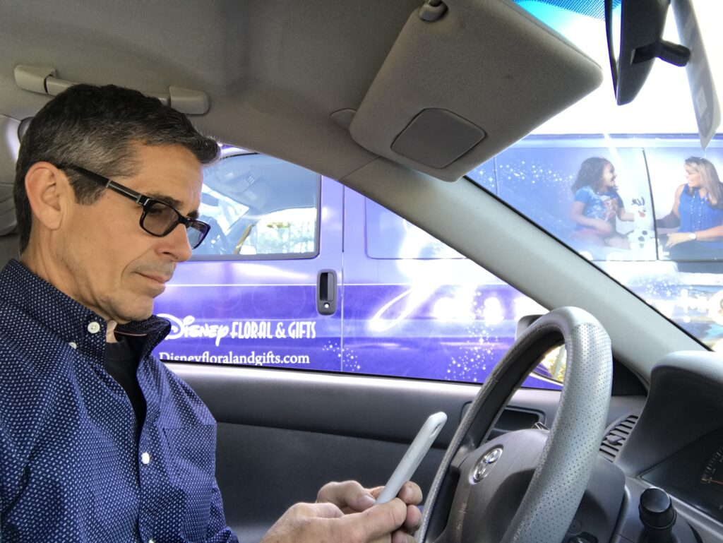 man sitting in parked car looking at phone